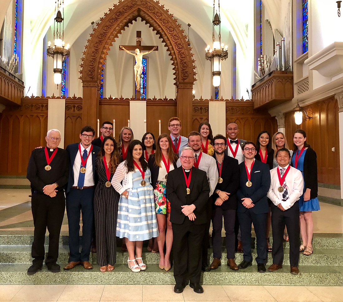 Winners of the 2018 St. Ignatius of Loyola Medal standing together at the front interior of Sacred Heart Chapel