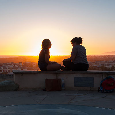 Two women facing each other by the sunset.